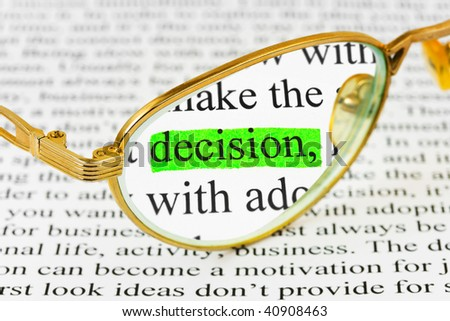 Glasses on business article and word decision - stock photo