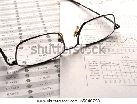 Glasses on the statement of financial analysis - stock photo