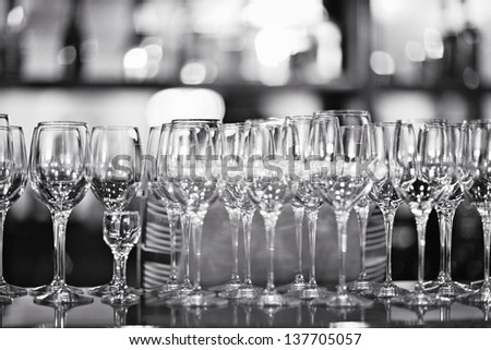 glasses on the table in a restaurant black and white - stock photo