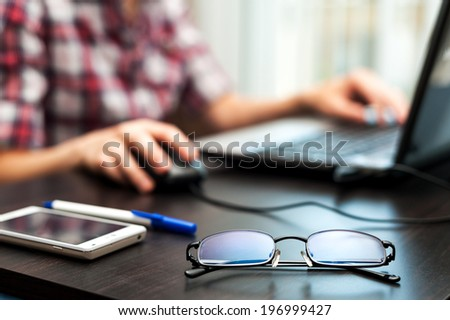 Glasses on the table with cell phone and student at work on the laptop - stock photo