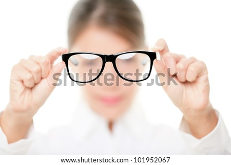Glasses - optician showing eyewear. Closeup of glasses, with glasses and frame in focus. Woman optometrist on white background. - stock photo