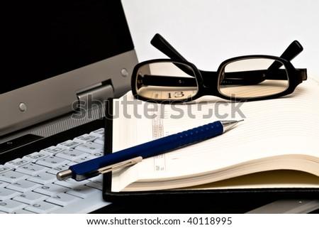 Glasses, pen and open agenda on laptop - stock photo