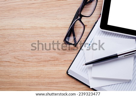 Glasses, pen, cell phone,notebook lie on light brown desktop - stock photo