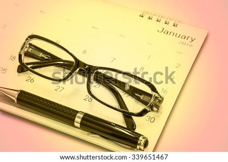 Glasses, pens, calendars isolated on white - stock photo
