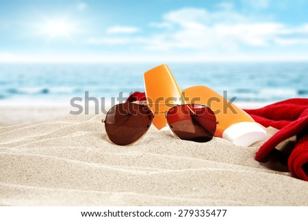 glasses red towel and sand  - stock photo