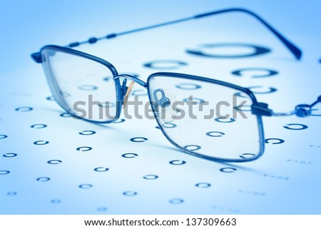 Glasses to improve vision on the test card. In blue tones. - stock photo