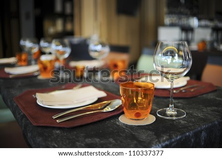 Glasses, Wine Glasses and plates on table in restaurant - stock photo