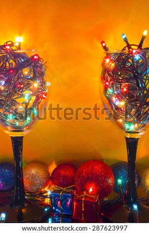 glasses with a yellow background garlands with Christmas toys and gifts - stock photo