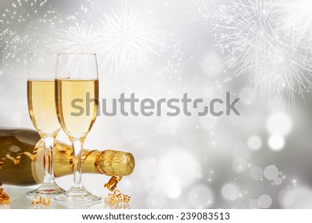 Glasses with champagne and bottle over fireworks and sparkling holiday background - stock photo