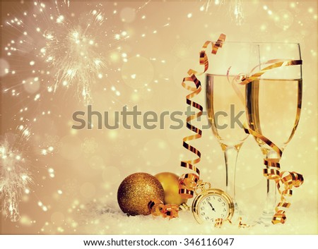 Glasses with champagne and Christmas decoration on sparkling background - stock photo