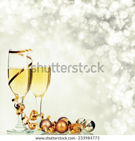 Glasses with champagne and christmas decorations on sparkling background - stock photo