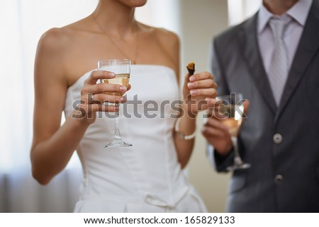 Glasses with champagne in hands of bride and groom. Shallow depth of field - stock photo