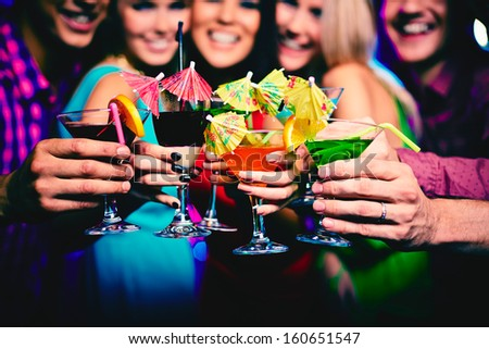 Glasses with cocktails held by happy friends at party - stock photo