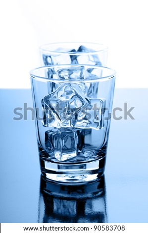 Glasses with crystal clear ice cubes on glossy background - stock photo