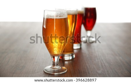 Glasses with different sorts of craft beer on wooden table - stock photo
