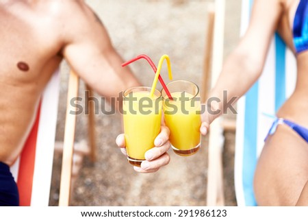 Glasses with fresh orange juice and straws held by couple - stock photo