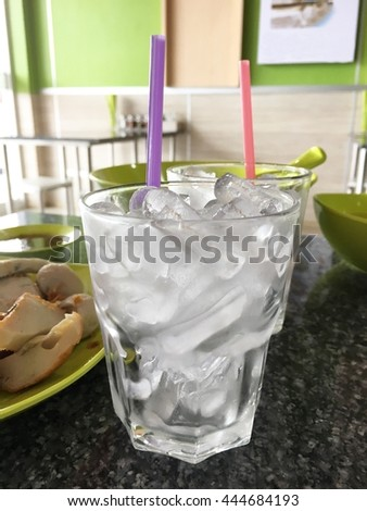Glasses with ice cubes and food on  table - stock photo