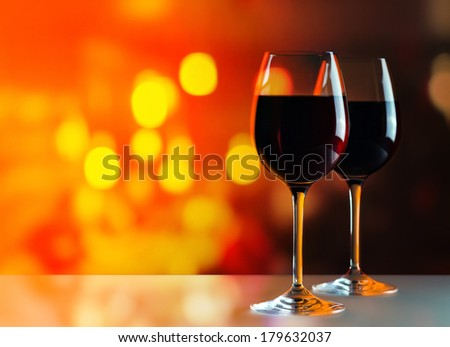 glasses with red wine on glass table - stock photo