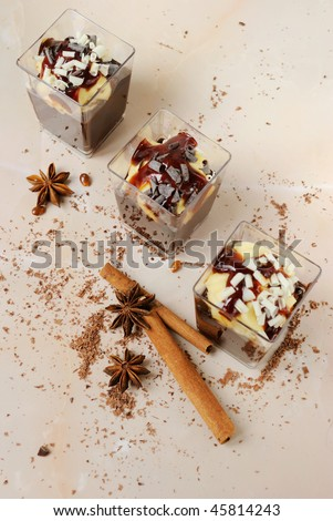 glasses with two color creamy desserts and species - stock photo