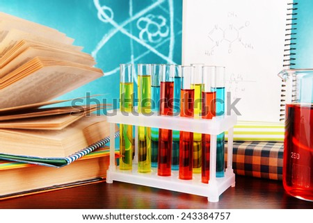 Glassware with chemical agent on desk, on green blackboard background - stock photo
