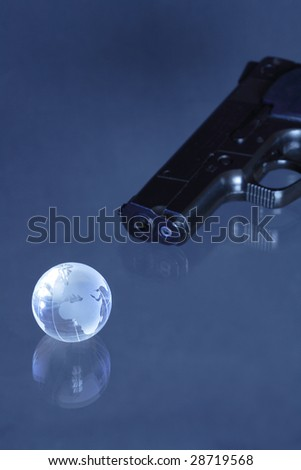 Glassy globe with pistol lying on dark background - stock photo