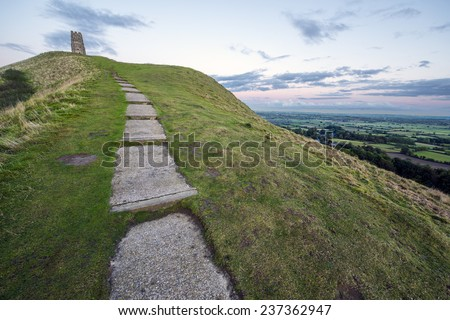 Glastonbury Tor is a hill at Glastonbury in the English county of Somerset, topped by the roofless St Michael's Tower - stock photo