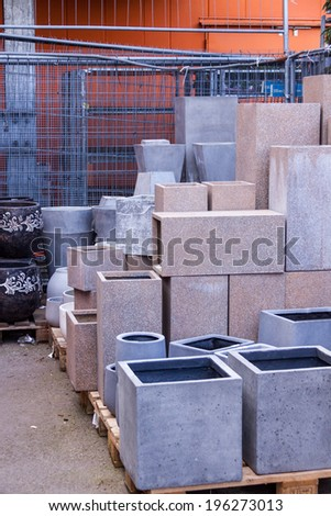 Glazed and unglazed ceramic flower pots in a variety of sizes and colors stacked on wooden pallets outside a pottery, warehouse or commercial store - stock photo