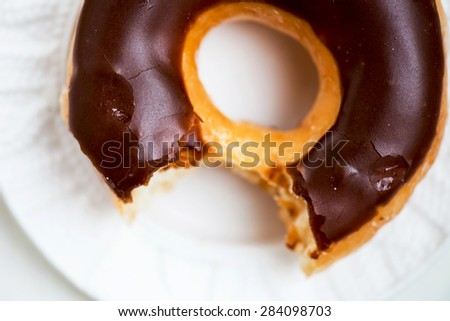 Glazed Donut with Bite Missing on white plate. Selective focus. Narrow DOF - stock photo