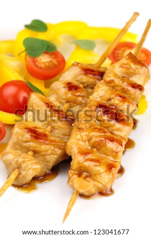 Glazed turkey breast skewers with bell pepper and tomato salad on white plate - stock photo