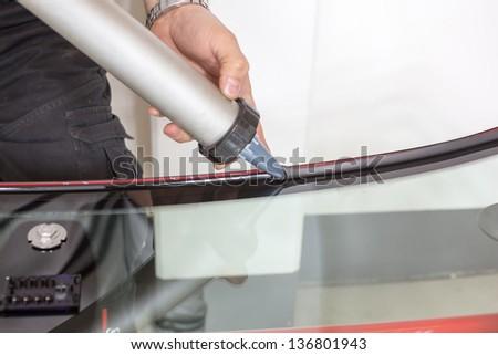 Glazier applying rubber sealing to windshield in garage - stock photo