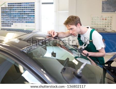 Glazier installs windscreen into car in garage - stock photo
