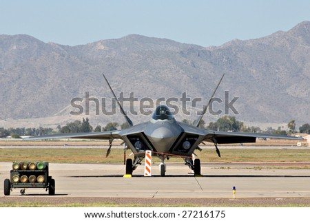 """GLENDALE, AZ - MARCH 21: A U.S. Air Force F-22 Raptor fighter parked on the runway at the biennial air show (""""Thunder in the Desert"""") at Luke Air Force Base on March 21, 2009 in Glendale, AZ. - stock photo"""