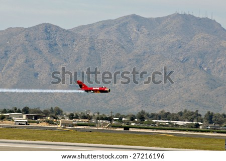 """GLENDALE, AZ - MARCH 21: Bill Reesman makes a low altitude pass in a Russian MiG-17 at the biennial air show (""""Thunder in the Desert"""") at Luke Air Force Base on March 21, 2009 in Glendale, AZ. - stock photo"""