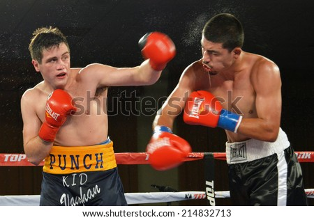 GLENDALE, CA - AUGUST 9, 2014: :Boxer Liam Vaughn follows through on a punch against his opponent Saul Benitez. The bout took place at Glendale Fight Night in Glendale, California on August 9, 2014. - stock photo