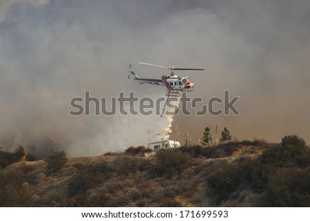 GLENDORA, CALIFORNIA, USA - JANUARY 16, 2014: A large wildfire burns out of control in the hills above Glendora. Firefighters, helicopters and aircraft from many jurisdictions work to control it. - stock photo