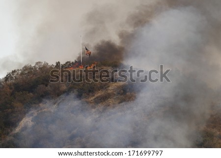 GLENDORA, CALIFORNIA, USA - JANUARY 16, 2014: A large wildfire burns out of control in the hills above Glendora. Firefighters, helicopters and aircraft from many jurisdictions work to control it . - stock photo
