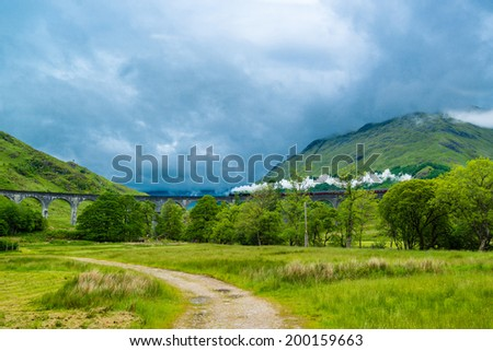 GLENFINNAN, SCOTLAND - June 5, 2014: A steam train on famous Glenfinnan viaduct, well known through Harry Potter as Hogwarts Express on June 5, 2014 in Glenfinnan, Scotland, Great Britain. - stock photo