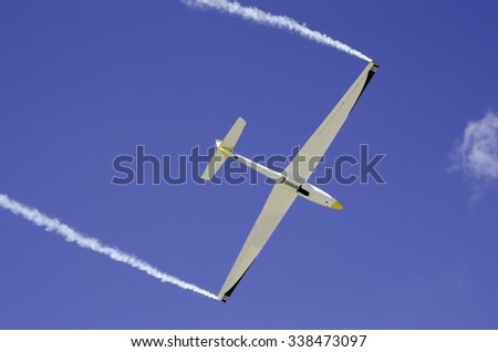 Glider blue sky smoke wings - stock photo