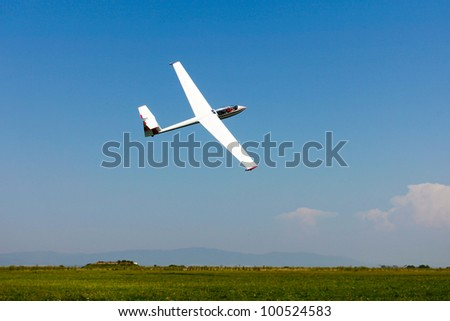 Glider flying on a blue sky - stock photo