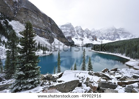 Glimmering crystal sapphire blue of Moraine Lake framed with ten snow peaks standing white-gray in morning fog Banff - stock photo