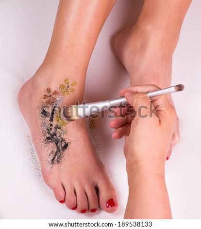 Glitter tattoo on a caucasian woman's leg. - stock photo