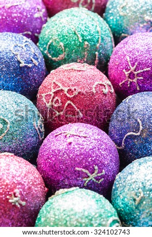 Glittering Christmas ornaments - Christmas ornaments with colorful glitter and simple festive artwork. Shallow DOF for use as background. Natural light used. - stock photo