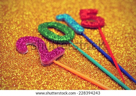 glittering numbers of different colors forming the number 2015, as the new year, on a shiny golden background - stock photo