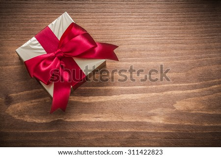 Glittery gold giftbox with red bow on vintage wooden board. - stock photo