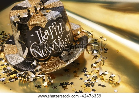 Glittery new year's hat with streamers and confetti shot on gold metallic background - stock photo