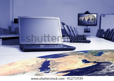 Global communication concept using video conferencing in boardroom - stock photo