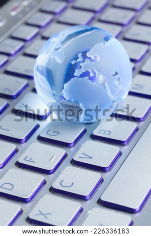 global computer business concept with small glass globe on laptop keyboard - stock photo
