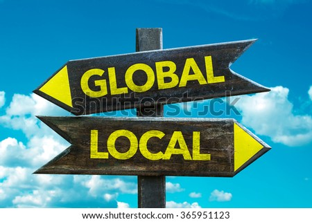 Global - Local signpost with sky background - stock photo