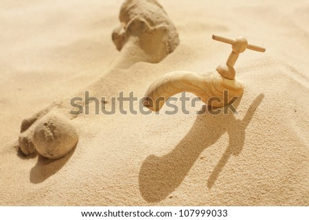 Global warming climate change faucet in the sand concept - stock photo