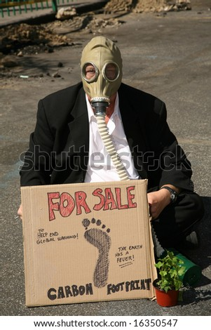 Global Warming concepts. a Business Man wears a Gas Mask and offers to sell his Carbon Footprint to help end Global Warming - stock photo